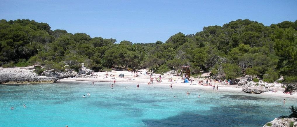 Plage de sable blanc à Minorque avec au premier plan la mer avec une eau turquoise et cristalline et à l'arrière plan la forêt.